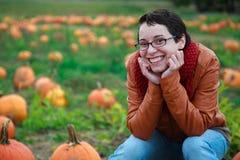 Lächelnde junge Frau im Kürbis-Flecken Stockbild