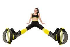 Lächelnde junge Frau im kangoo springt die Schuhe, die auseinander Beine sitzen lizenzfreies stockfoto