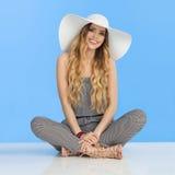 Lächelnde junge Frau im Overall, in weißem Sun-Hut und in den hohen Absätzen sitzt mit den gekreuzten Beinen Lizenzfreie Stockbilder