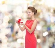 Lächelnde junge Frau im roten Kleid mit Geschenkbox stockfoto