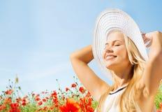 Lächelnde junge Frau im Strohhut auf Mohnblumenfeld Stockfotos