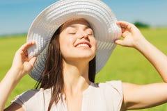 Lächelnde junge Frau im Strohhut draußen Lizenzfreie Stockbilder