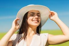 Lächelnde junge Frau im Strohhut draußen Lizenzfreies Stockbild