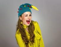 Lächelnde junge Frau im Weihnachtshut lokalisiert auf dem grauen Blinzeln Stockbilder