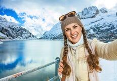 Lächelnde junge Frau im Winter Alto Adige, Italien, das selfie nimmt Stockfotografie