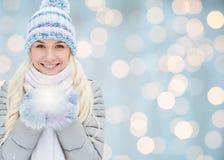 Lächelnde junge Frau im Winter kleidet über Lichtern lizenzfreies stockfoto