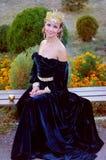 Lächelnde junge Frau kleidete wie die Königin an, die einen Apfel hält Lizenzfreies Stockfoto
