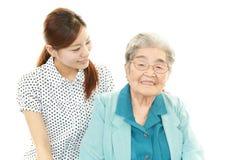 Lächelnde junge Frau mit alter Dame Lizenzfreie Stockbilder
