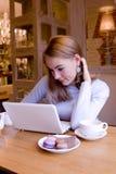 Lächelnde junge Frau mit Computer am breacfast Stockbild