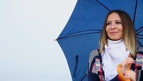 Lächelnde junge Frau mit dem blauen Regenschirmblinzeln stock footage