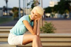 Lächelnde junge Frau mit dem kurzen blonden Haar, das draußen sitzt Stockbild