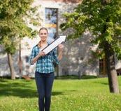 Lächelnde junge Frau mit dem Pfeil, der oben poiting ist Stockfoto