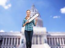 Lächelnde junge Frau mit dem Pfeil, der oben poiting ist Lizenzfreie Stockfotos