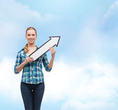 Lächelnde junge Frau mit dem Pfeil, der oben poiting ist Lizenzfreies Stockfoto