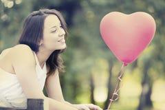 Lächelnde junge Frau mit einem roten geformten Herzen Lizenzfreies Stockbild