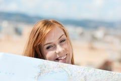 Lächelnde junge Frau mit einer Karte Lizenzfreies Stockfoto