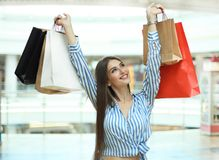 Lächelnde junge Frau mit Einkaufstaschen über Mallhintergrund lizenzfreie stockfotografie