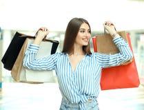 Lächelnde junge Frau mit Einkaufstaschen über Mallhintergrund lizenzfreie stockbilder
