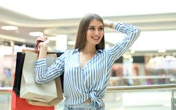 Lächelnde junge Frau mit Einkaufstaschen über Mallhintergrund stockfoto