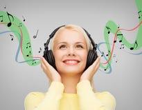 Lächelnde junge Frau mit Kopfhörern Lizenzfreie Stockfotografie