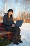 Lächelnde junge Frau mit Laptop im Winter lizenzfreies stockfoto