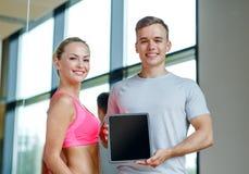 Lächelnde junge Frau mit persönlichem Trainer in der Turnhalle Lizenzfreie Stockfotos