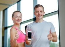 Lächelnde junge Frau mit persönlichem Trainer in der Turnhalle Lizenzfreies Stockfoto