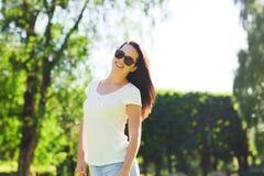 Lächelnde junge Frau mit Sonnenbrille im Park Stockfoto