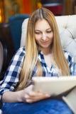 Lächelnde junge Frau mit Tablette zu Hause Lizenzfreie Stockbilder