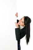 Lächelnde junge Frau mit unbelegtem Zeichen Stockbild