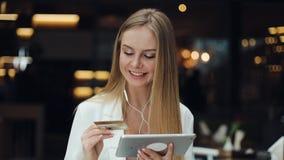 Lächelnde junge Frau nimmt Daten von der goldenen Kreditkarte, die mit einer Tablette arbeitet stock footage