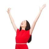 Lächelnde junge Frau in rotes Kleiderwellenartig bewegenden Händen Lizenzfreie Stockbilder