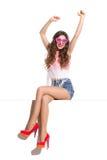 Lächelnde junge Frau sitzt auf einer Spitze und dem Anheben von Armen Lizenzfreies Stockfoto