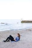 Lächelnde junge Frau steht auf Strand still und wirft in camera auf und sitzt stockfotos