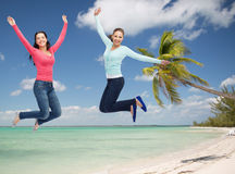 Lächelnde junge Frauen, die in einer Luft springen Stockfotografie