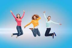 Lächelnde junge Frauen, die in einer Luft springen Stockfoto
