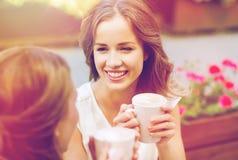 Lächelnde junge Frauen mit Kaffeetassen am Café Stockbilder