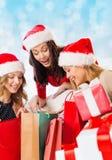 Lächelnde junge Frauen in Sankt-Hüten mit Geschenken Stockfoto