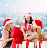 Lächelnde junge Frauen in Sankt-Hüten mit Geschenken Stockbild