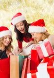 Lächelnde junge Frauen in Sankt-Hüten mit Geschenken Lizenzfreie Stockfotografie
