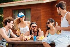 Lächelnde junge Freunde, die draußen Bier sitzen und trinken stockfotos