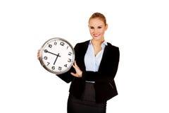 Lächelnde junge Geschäftsfrau, die Bürouhr hält Stockfoto