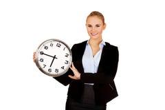 Lächelnde junge Geschäftsfrau, die Bürouhr hält Stockbild