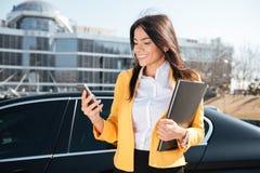 Lächelnde junge Geschäftsfrau mit Dokumenten im Ordner unter Verwendung des Smartphone draußen Stockfoto