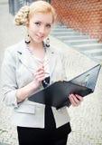 Lächelnde junge Geschäftsfrau mit Faltblatt in den Händen Stockfotografie