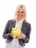 Lächelnde junge Geschäftsfrau mit Sparschwein Stockfoto