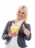 Lächelnde junge Geschäftsfrau mit Sparschwein und dem Daumen oben Stockfoto