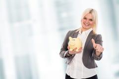 Lächelnde junge Geschäftsfrau mit Sparschwein und dem Daumen oben Lizenzfreies Stockbild