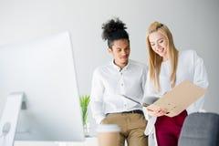 lächelnde junge Geschäftskollegen, die Ordner mit Dokumenten betrachten Stockfoto