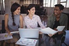 Lächelnde junge Geschäftsleute, die im Büro zusammenarbeiten stockfotos